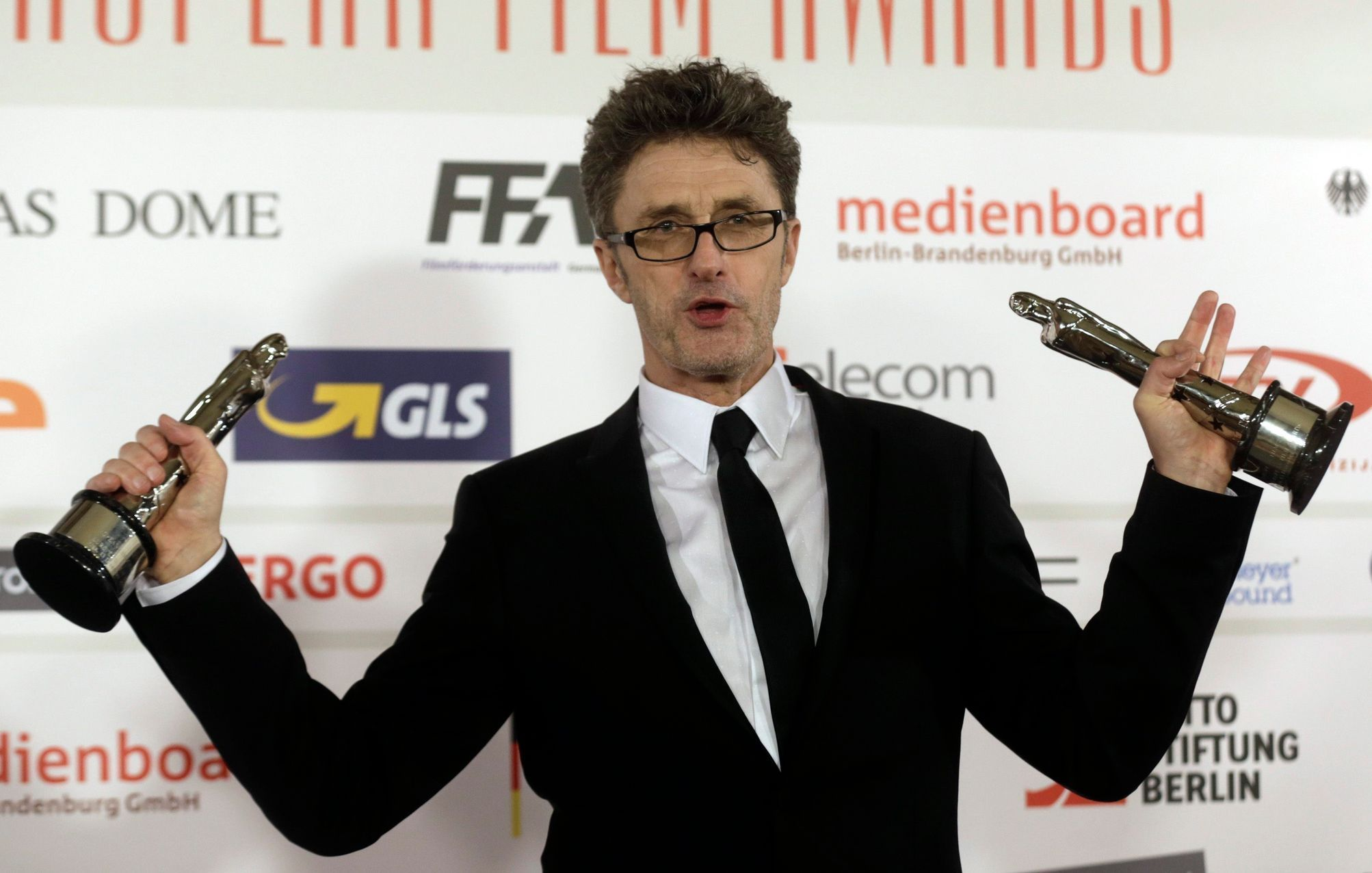 "Pawlikowski poses with his trophies for European director and screenwriter for his work in the movie ""Ida"" after the European Film Awards ceremony in Riga"