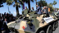 "Cast members Arnold Schwarzenegger, Jason Statham and Harrison Ford pose on a tank as they arrive on the Croisette to promote the film ""The Expendables 3"" during the 67th Cannes Film Festiva"