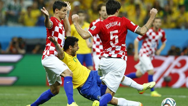 Brazil's Fred (C) is fouled by Croatia's Dejan Lovren (L) during the 2014 World Cup opening match between Brazil and Croatia at the Corinthians arena in Sao Paulo June 12