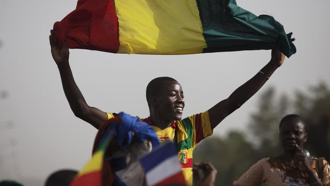 A Malian man waves a Mali flag as France's President Francois Hollande (not pictured) speaks at Independence Plaza in Bamako, Mali February 2, 2013. France will withdraw its troops from Mali once the Sahel state has restored sovereignty over its national territory and a U.N.-backed African military force can take over from the French soldiers, Hollande said on Saturday. REUTERS/Joe Penney (MALI - Tags: POLITICS CONFLICT) Published: Úno. 2, 2013, 8:07 odp.