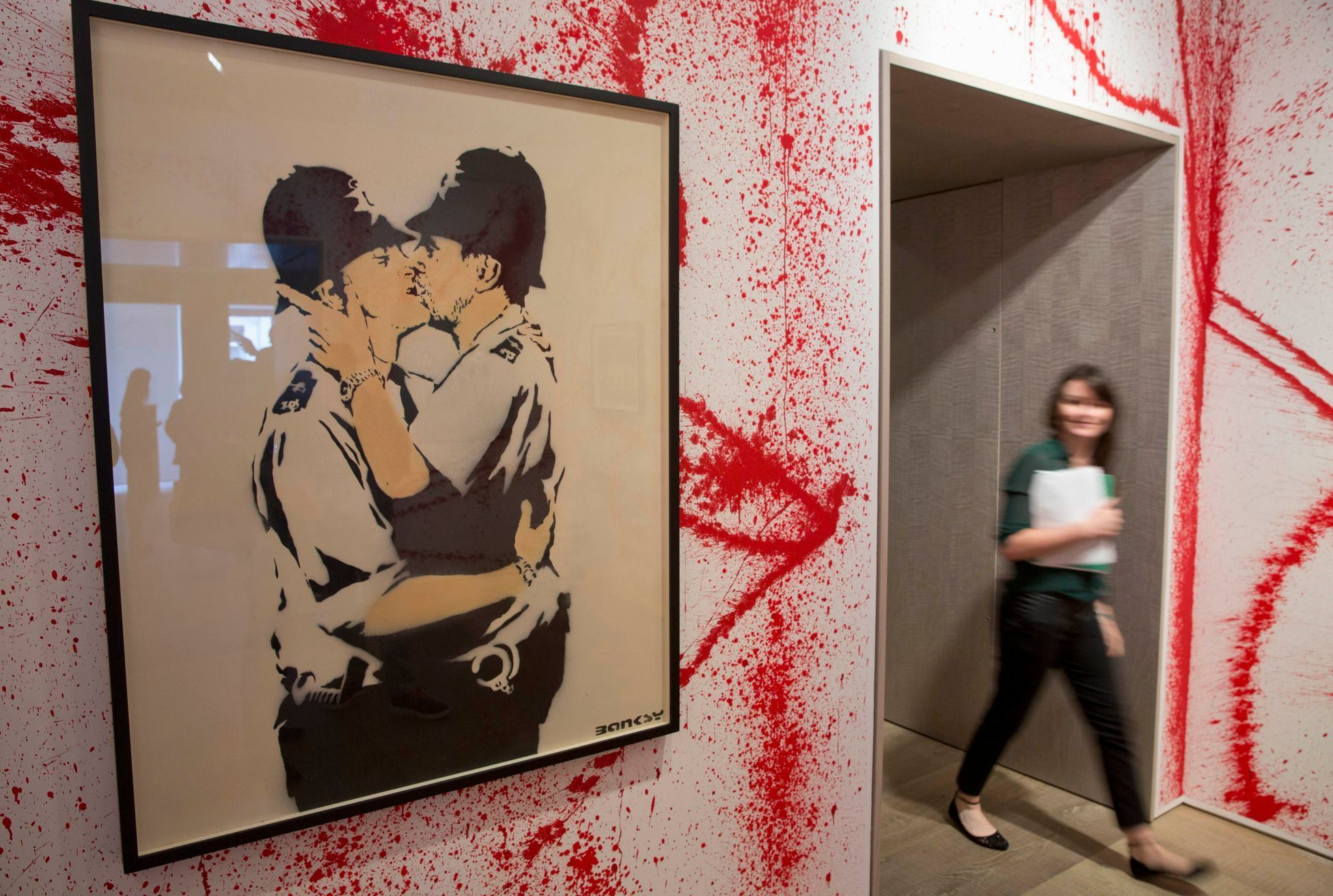 "Woman walks past ""Kissing Coppers"" by artist Banksy at Banksy: The Unauthorised Retrospective at Sotheby's S2 Gallery in London June 06, 2014. REUTERS/Neil Hall (BRITAIN)"