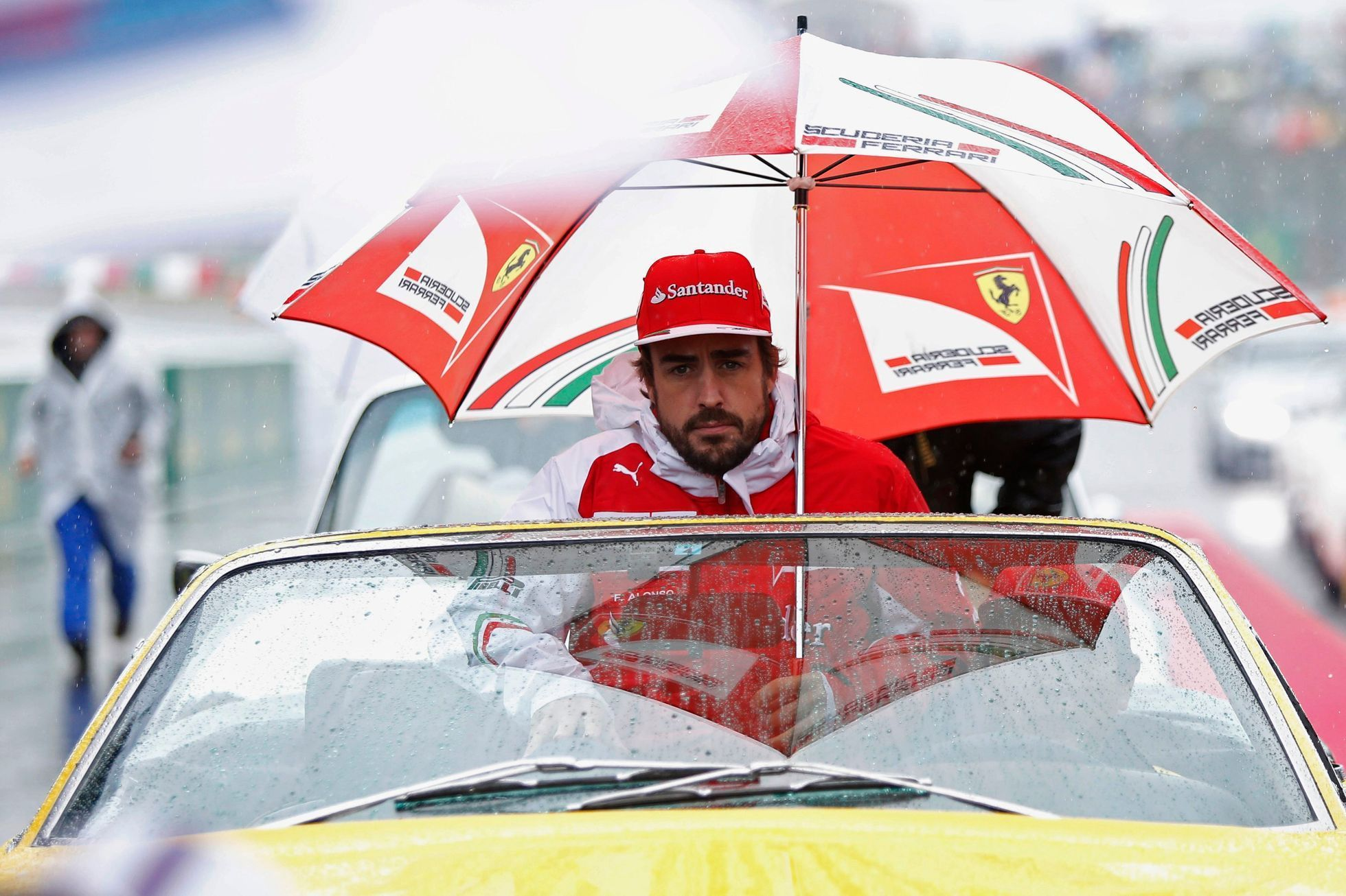 Ferrari Formula One driver Fernando Alonso of Spain sits under an umbrella during the drivers' parade ahead of the Japanese F1 Grand Prix at the Suzuka Circuit