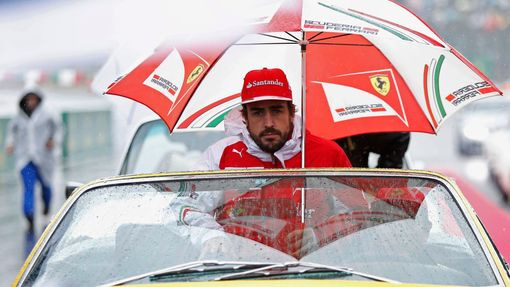 Ferrari Formula One driver Fernando Alonso of Spain sits under an umbrella during the drivers' parade ahead of the Japanese F1 Grand Prix at the Suzuka Circuit October 5,