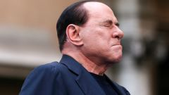 File photo of Berlusconi closing his eyes in a gesture to supporters during a rally to protest his tax fraud conviction, outside his palace in central Rome