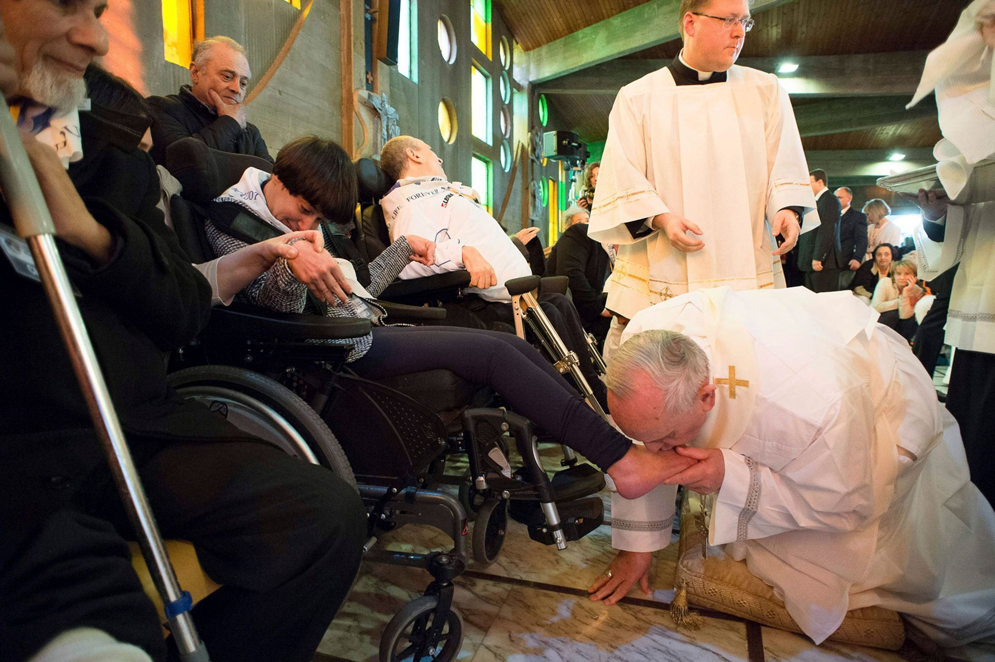 Pope Francis kisses the foot of a disabled person at the S. Maria della Provvidenza church in Rome, during Holy Thursday celebration
