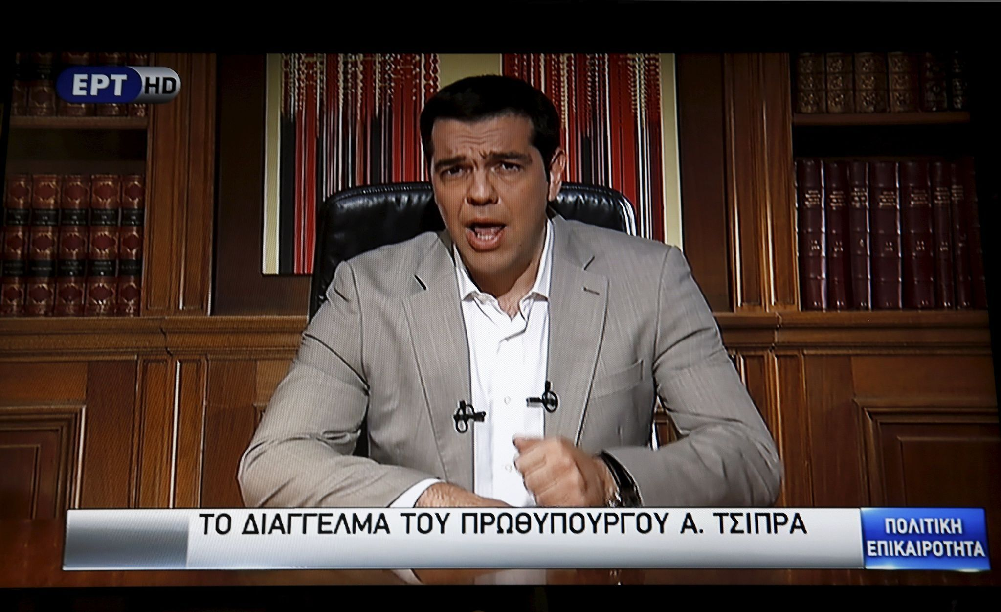 Greek Prime Minister Alexis Tsipras is seen on a television monitor while addressing the nation in Athens, Greece
