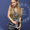 Recording artist Ariana Grande poses backstage with her award for best pop video during the 2014 MTV Video Music Awards in Inglewood