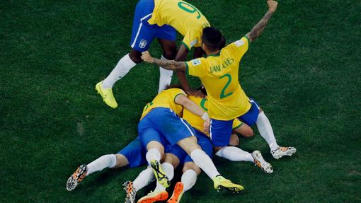 Brazil's players celebrate a goal by teammate Oscar (bottom, obscured) against Croatia during their 2014 World Cup opening match at the Corinthians arena in Sao Paulo Jun
