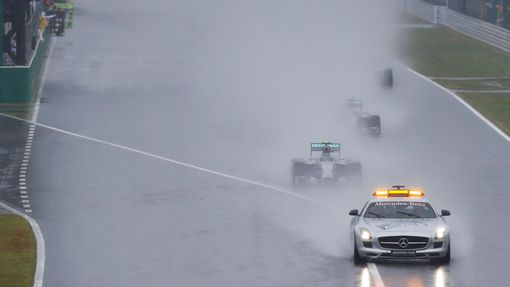 Mercedes Formula One driver Nico Rosberg of Germany leads team mate Lewis Hamilton of Britain behind a safety car as they start the first lap of the rain-affected Japanes