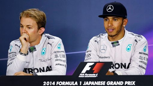 Mercedes Formula One driver Lewis Hamilton of Britain and teammate Nico Rosberg (L) of Germany attend a news conference after the Japanese F1 Grand Prix at the Suzuka Cir
