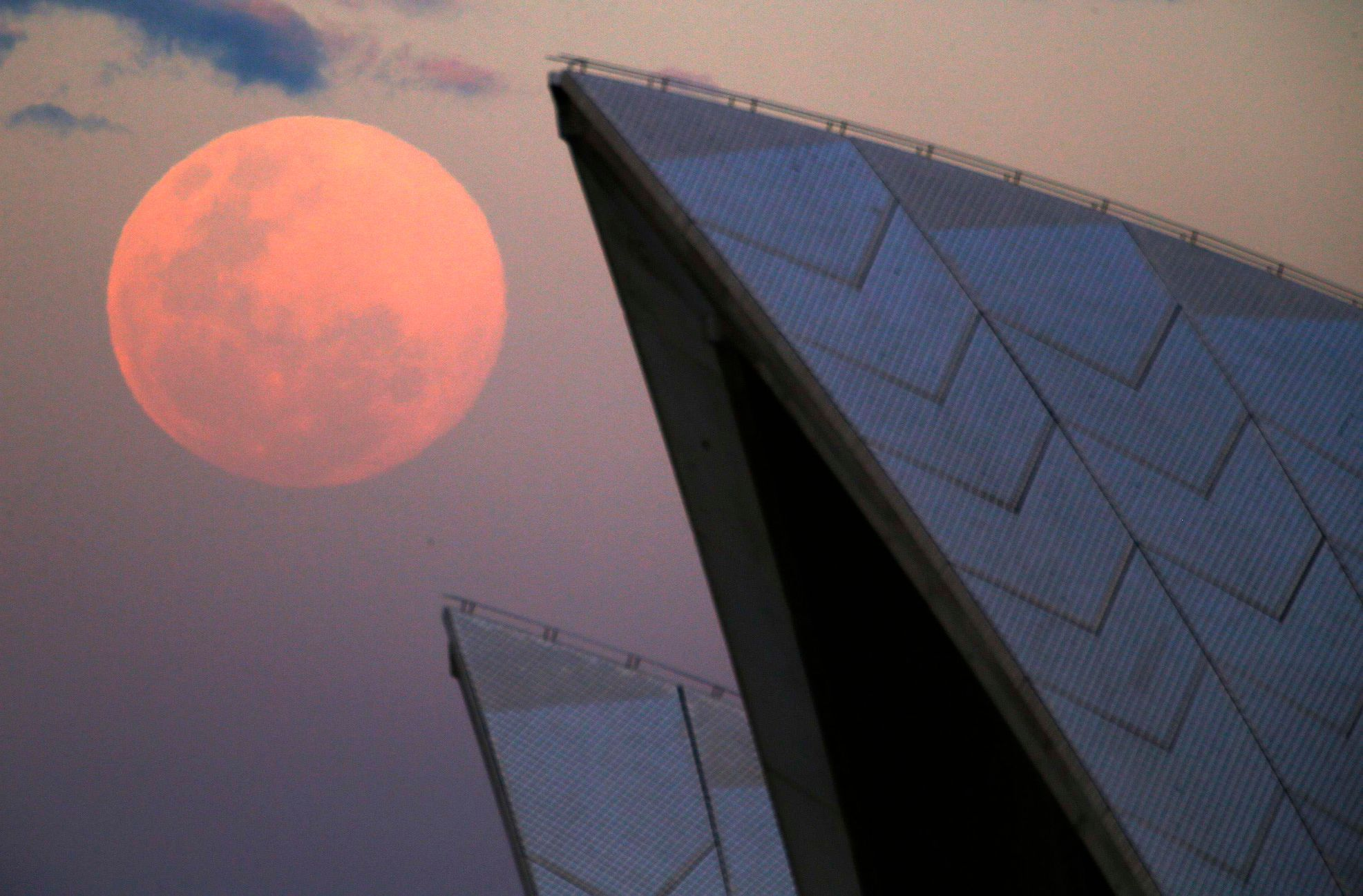 A supermoon rises behind the roof of the Sydney Opera House