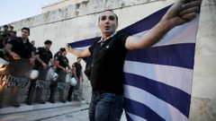 Řecko An anti-EU protester unfurls a Greek national flag next to riot police guarding the steps in front of the parliament building during a demonstration of about five hundred people in Athens
