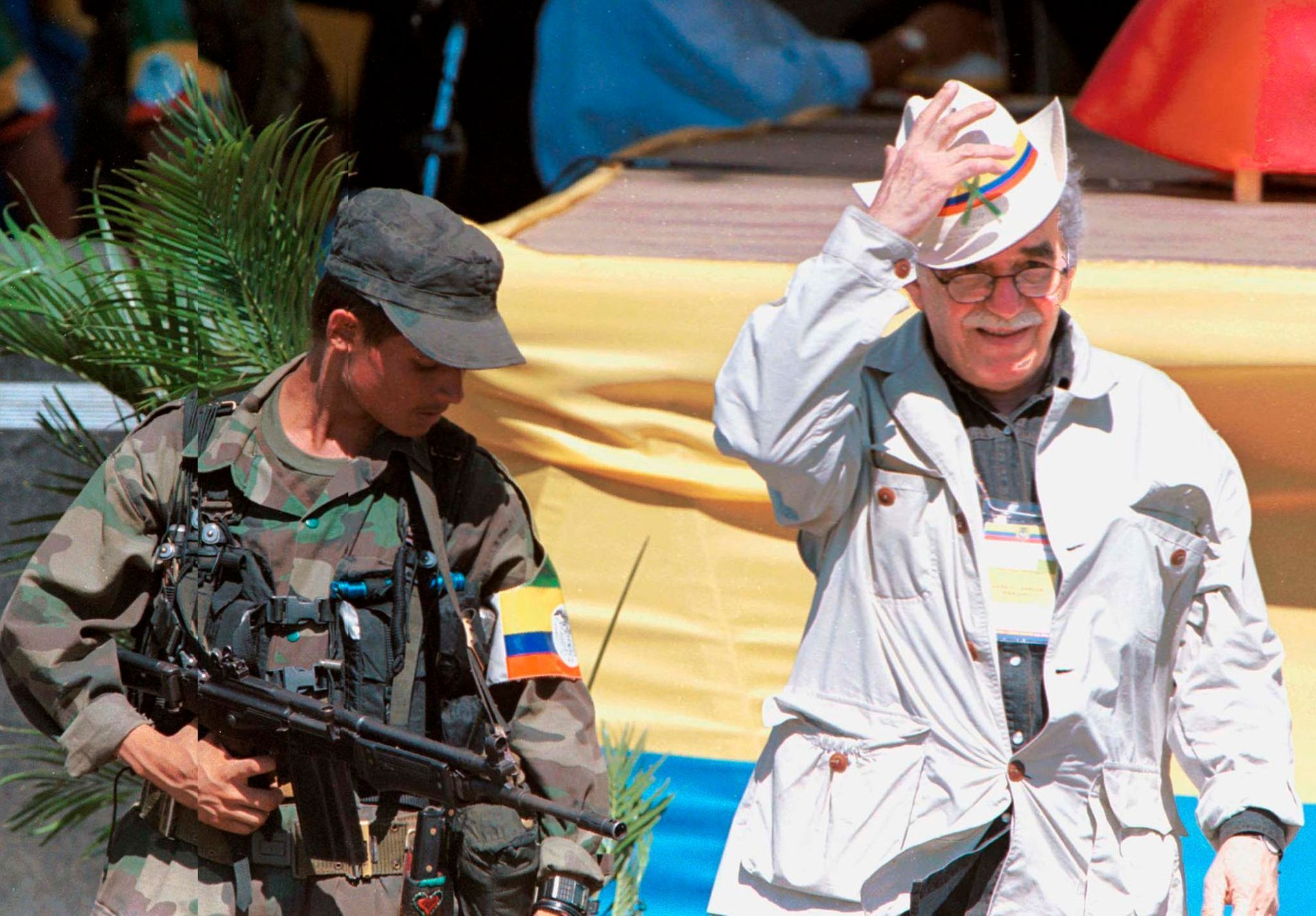 Colombian Nobel Prize laureate Garcia Marquez walks alongside a leftist rebel during the opening of the peace talks in San Vicente del Caguan