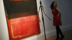 "Staff member poses in a gallery near ""No. 21 (Red, Brown, Black and Orange)"" by Rothko and ""Chariot"" by Giacometti at Sotheby's auction house in London"