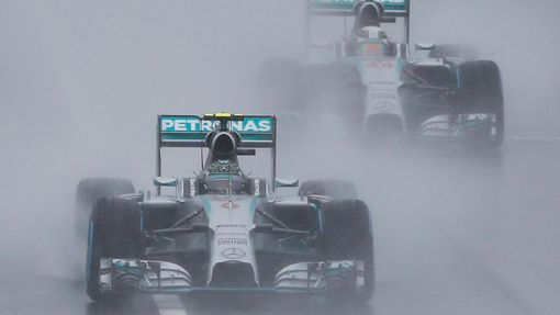 Mercedes Formula One driver Nico Rosberg of Germany leads team mate Lewis Hamilton of Britain behind a safety car (unseen) as they start the first lap of the rain-affecte