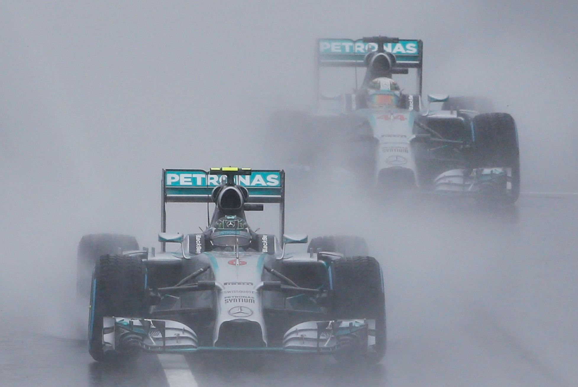 Mercedes Formula One driver Rosberg of Germany leads team mate Hamilton of Britain behind a safety car as they start the first lap of the rain-affected Japanese F1 Grand Prix at the Suzuka Circuit