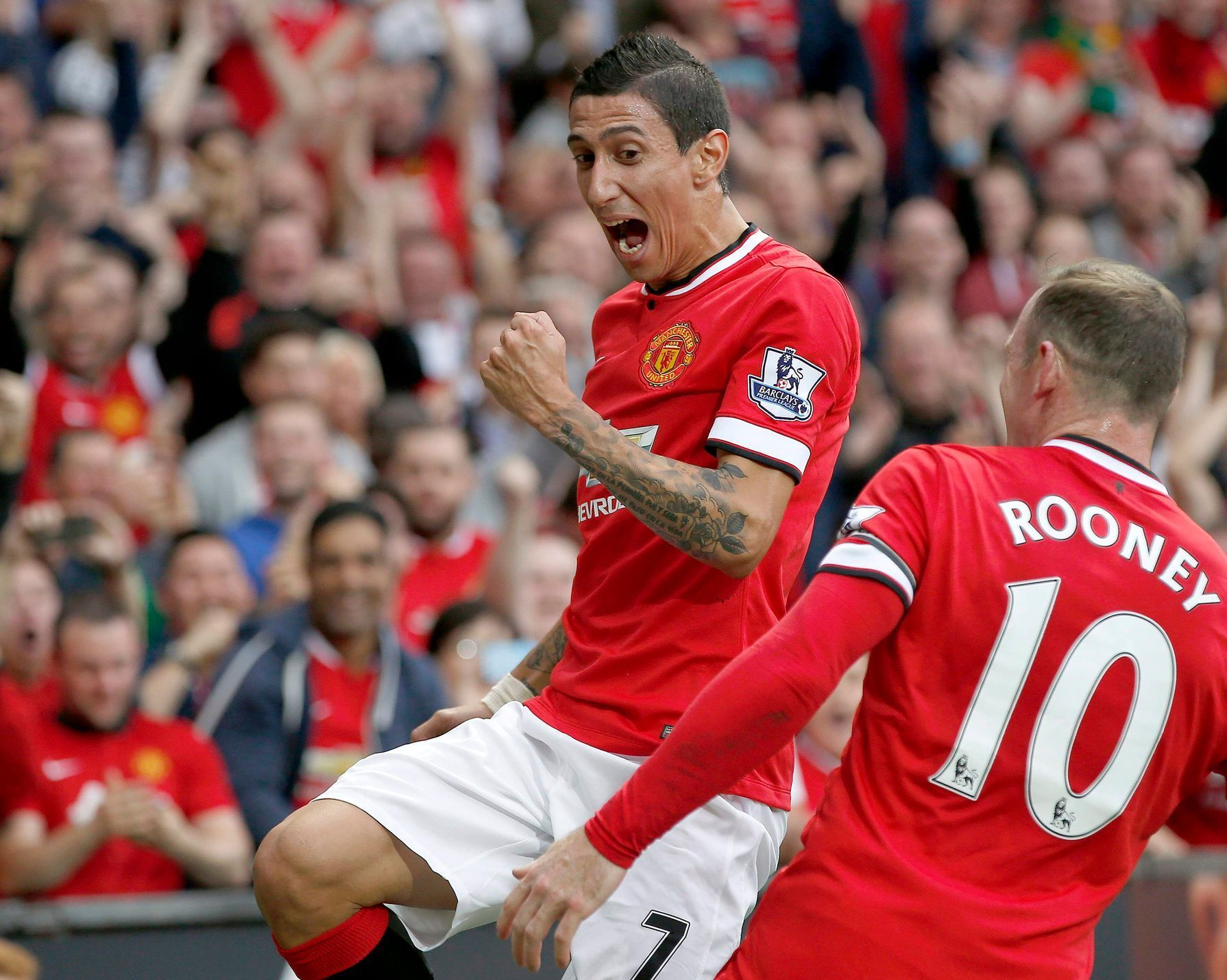 Manchester United's Di Maria celebrates with teammate Rooney after scoring a goal against Queens Park Rangers during their English Premier League soccer match at Old Trafford in Manchester