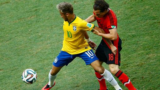 Brazil's Neymar has his arm held on to by Mexico's Andres Guardado (R) during their 2014 World Cup Group A soccer match at the Castelao arena in Fortaleza, June 17, 2014.
