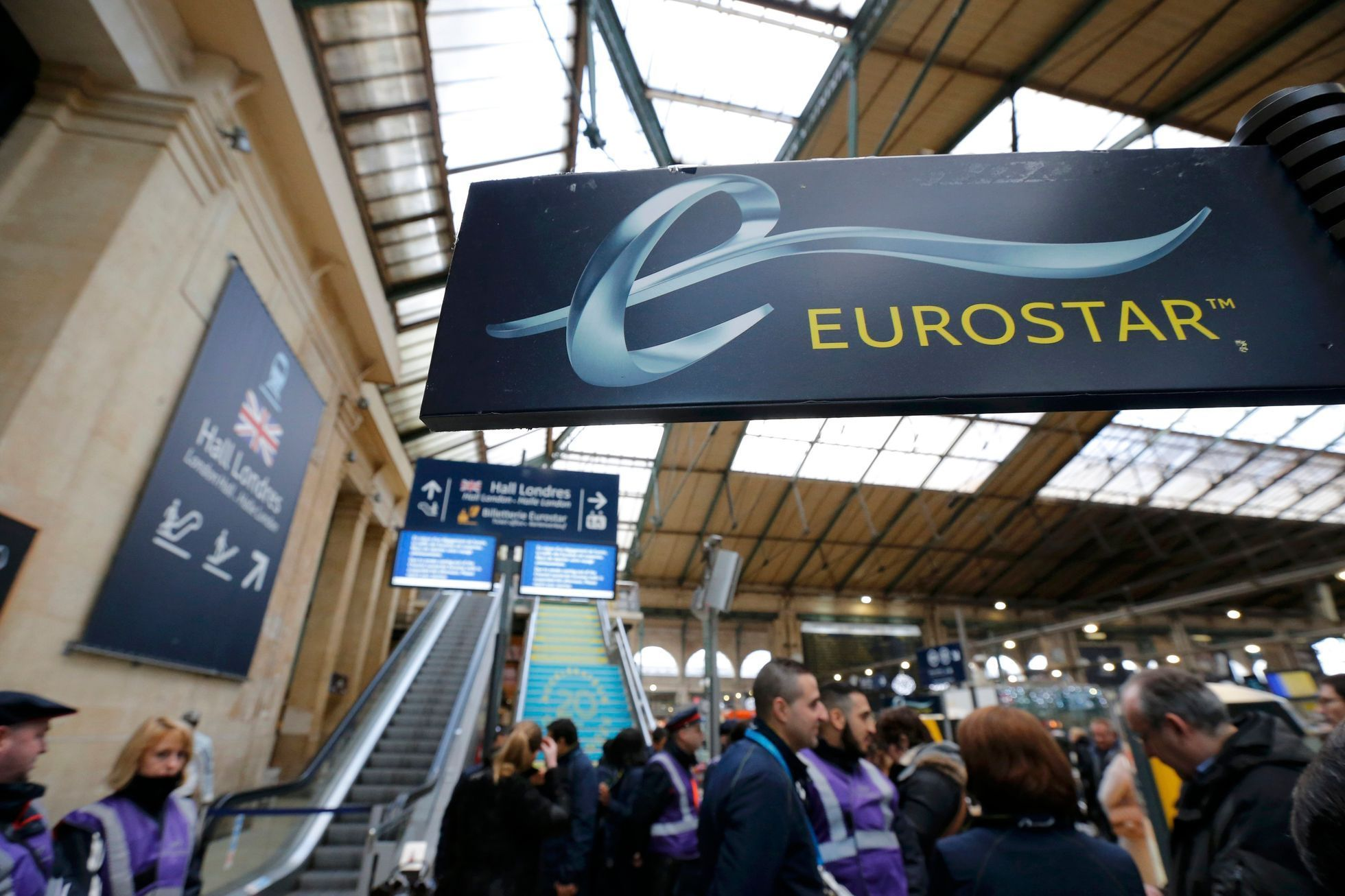 Passengers gather near the departure escalators at the Gare du Nord train station after the suspension of Eurostar rail traffic due to smoke coming out of the Channel tunnel