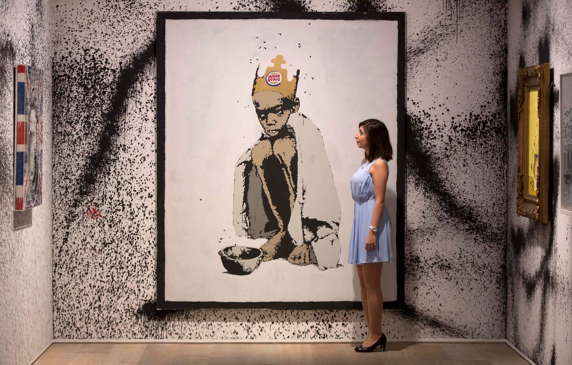A gallery assistant poses with Banksy painting at Banksy: The Unauthorised Retrospective exhibition at Sotheby's S2 Gallery in London