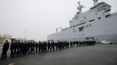 Russian sailors walk in front of the Mistral-class helicopter carrier Vladivostok at the STX Les Chantiers de l'Atlantique shipyard site in Saint-Nazaire