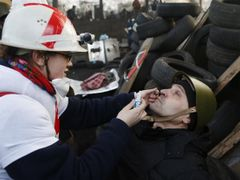 A medic cleans the eyes of an anti-government protester as he mans a barricade in Kiev February 21, 2014.