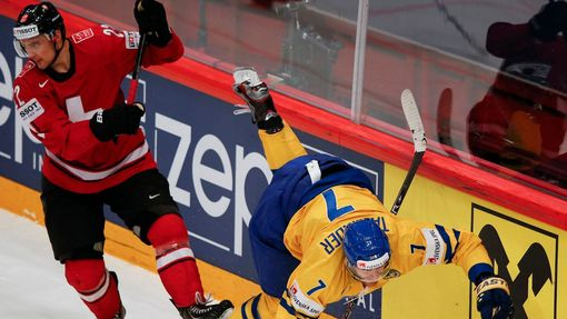 Switzerland's Nino Niederreiter fights for the puck with Sweden's Henrik Tallinder (R) during their 2013 IIHF Ice Hockey World Championship final match at the Globe Arena