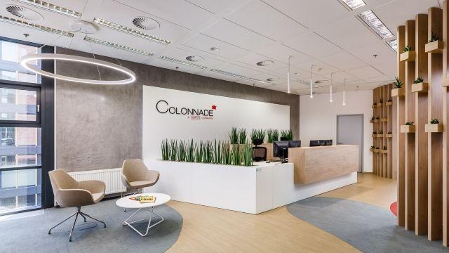 Moderní recepce společnosti Colonnade s posezením a dělícími dřevěnými lamelami se zelení.