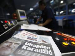 "A worker checks the new issue of the day's newspaper, featuring Radovan Karadzic on the front page, in Belgrade July 22, 2008. Karadzic, one of the world's most wanted men, has been arrested, a statement from the office of Serbian President Boris Tadic said on Monday. The headline reads: ""Karadzic arrested"". REUTERS/Marko Djurica (SERBIA)"
