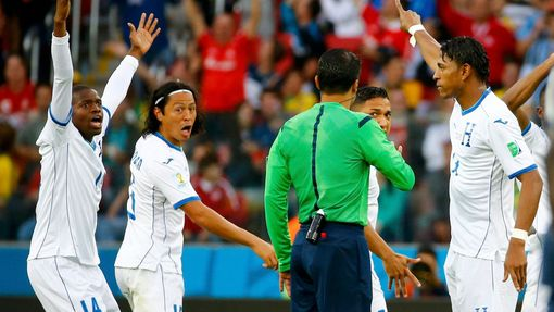 Honduras players argue with referee Sandro Ricci of Brazil after a controversial goal decision during their 2014 World Cup Group E soccer match against France at the Beir