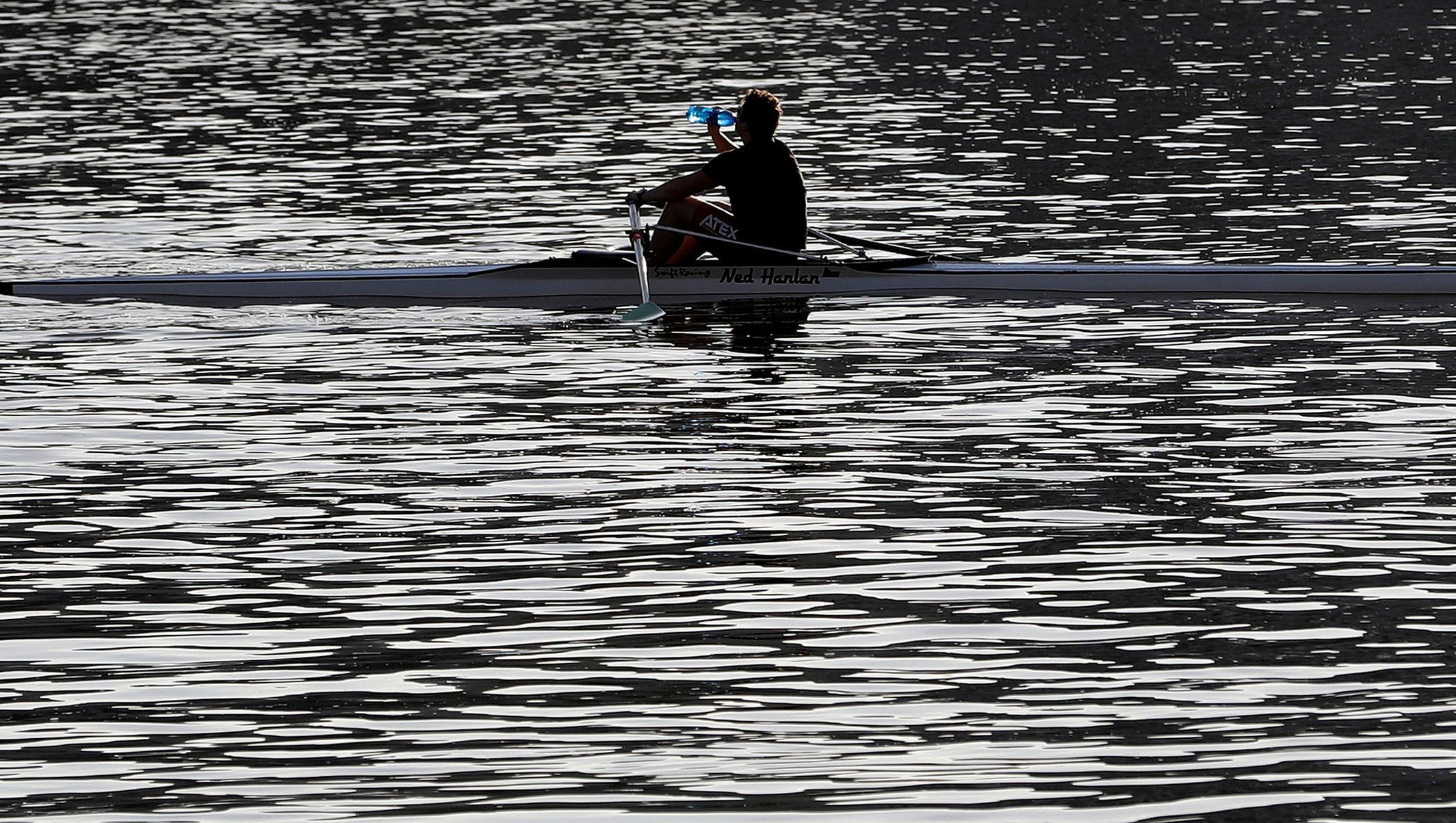 A man drinks a water as he rows a boat on the Vltava river in Prague
