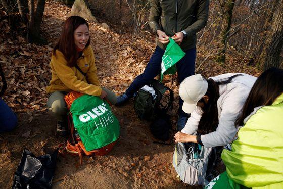 Členové spolku Clean Hikers odpadky nejdřív s pomocí ocelových kleští sbírají a dávají je do igelitových pytlů.