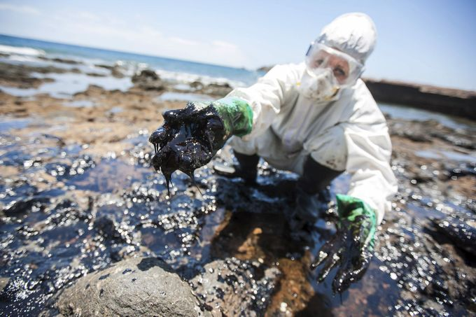 "A volunteer collects fuel oil from rocks at the ""Muelle Viejo"" beach in Gran Canaria in Spain's Canary Islands"