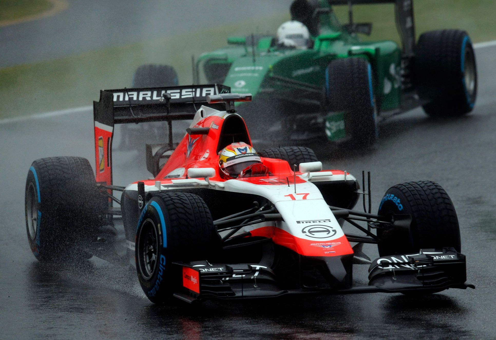 Marussia Formula One driver Bianchi of France drives in front of Caterham Formula One driver Kobayashi of Japan during the Japanese F1 Grand Prix at the Suzuka Circuit