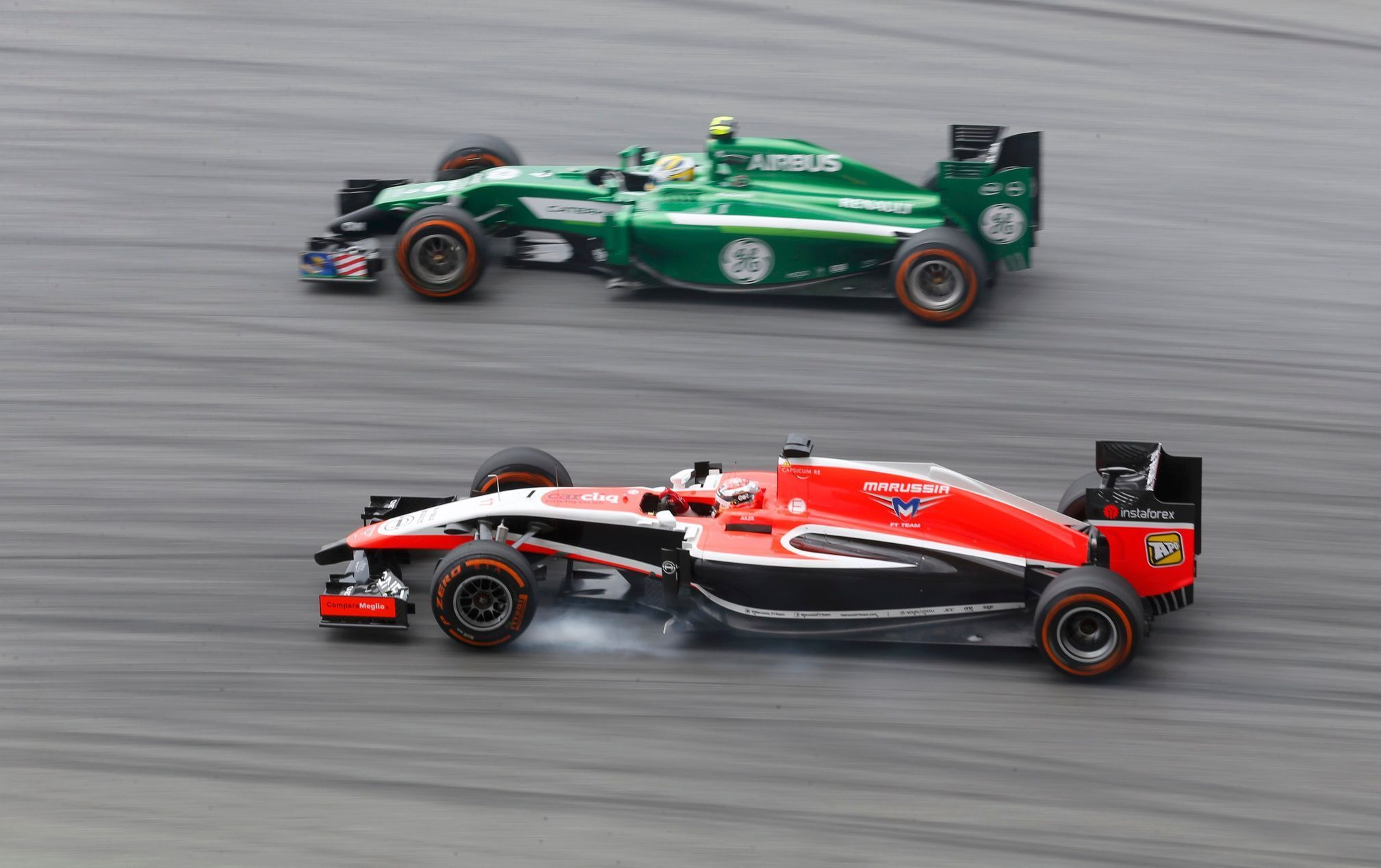 Marussia Formula One driver Bianchi passes Caterham Formula One driver Ericsson during the first practice session of the Malaysian F1 Grand Prix at Sepang International Circuit outside Kuala Lumpur