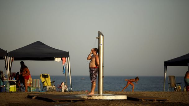 A man takes a shower during the second heat wave of the summer on Sacaba beach in Malaga