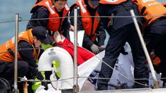South Korean coastguard officers recover a body on their vessel at the site where the capsized passenger ship Sewol sank in the sea off Jindo