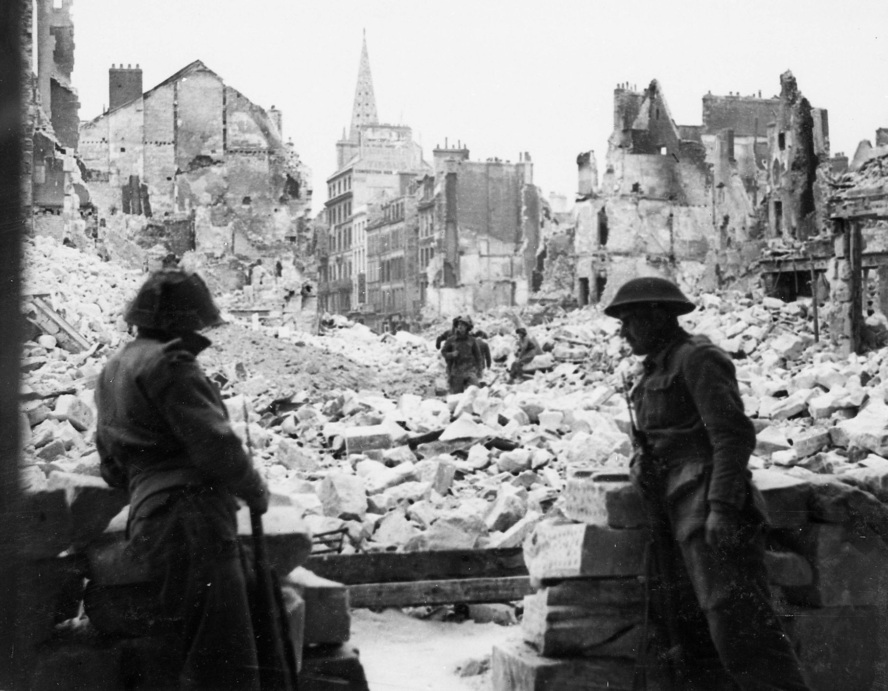 British troops keep watch across a destroyed square from a doorway of a cathedral after finally dislodging German forces from Caen