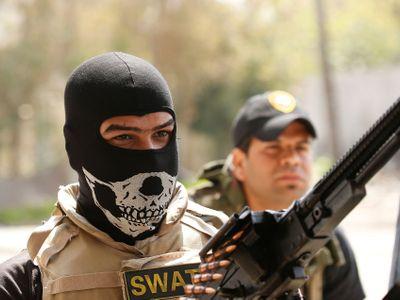 Iráčtí vojáci stojí před hlavní mešitou Islámského státu. V úzkých uličkách Mosulu umírají civilisté