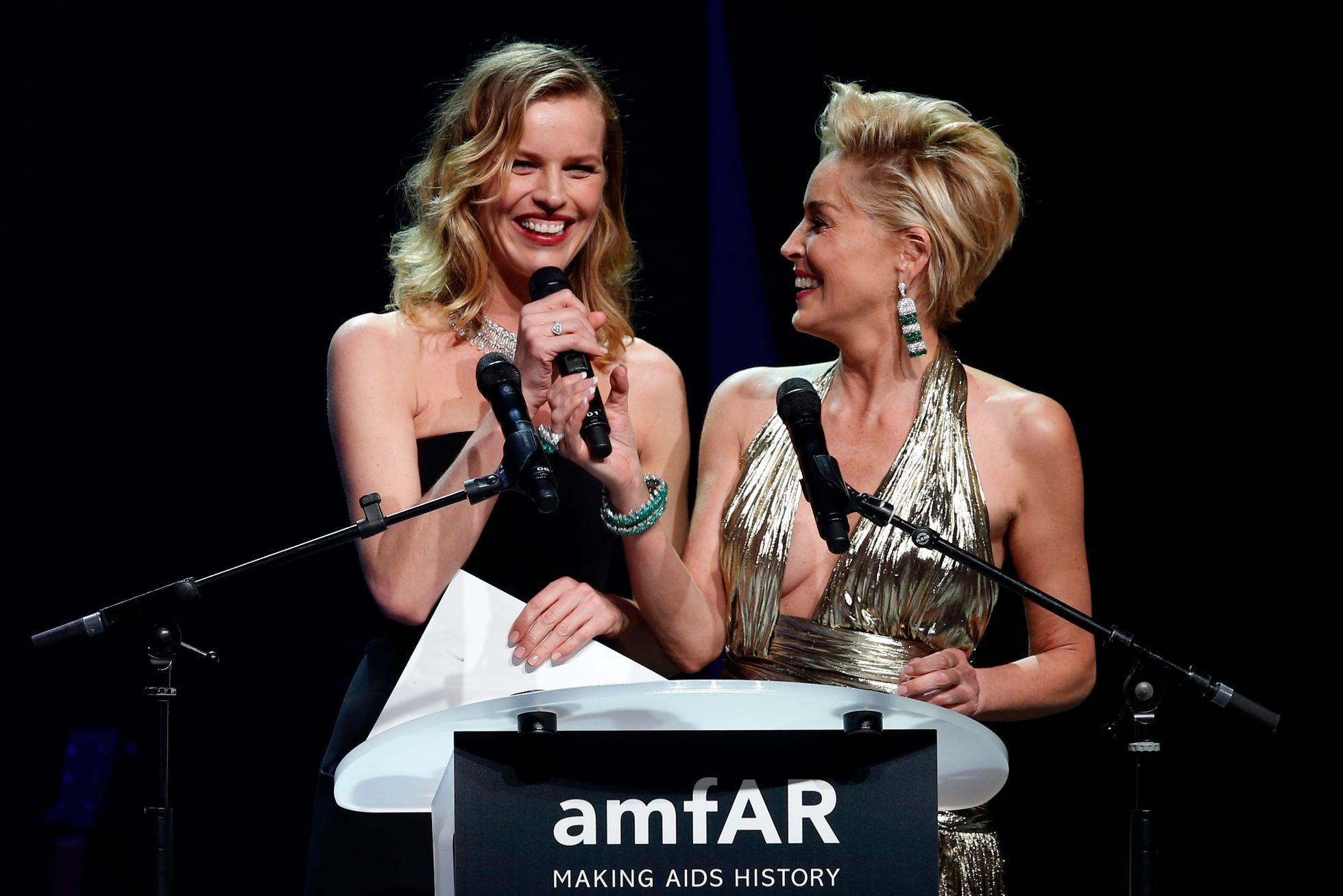 Model Herzigova of the Czech Republic and actress Stone of the U.S. attend an auction at the amfAR's Cinema Against AIDS 2014 event in Antibes