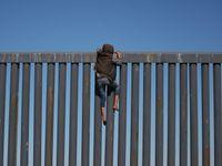 Obrazem: Šplhání po hraniční zdi i spaní na ulici. Karavana migrantů dorazila k USA