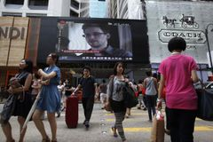 People cross a street in front of a monitor showing file footage of Edward Snowden, a former contractor for the U.S. National Security Agency (NSA), with a news tag (L) saying he has left Hong Kong, outside a shopping mall in Hong Kong June 23, 2013. Snowden left Hong Kong on a flight for Moscow on Sunday and his final destination may be Ecuador or Iceland, the South China Morning Post said. REUTERS/Bobby Yip (CHINA - Tags: POLITICS MEDIA) Published: Čer. 23, 2013, 8:35 dop.