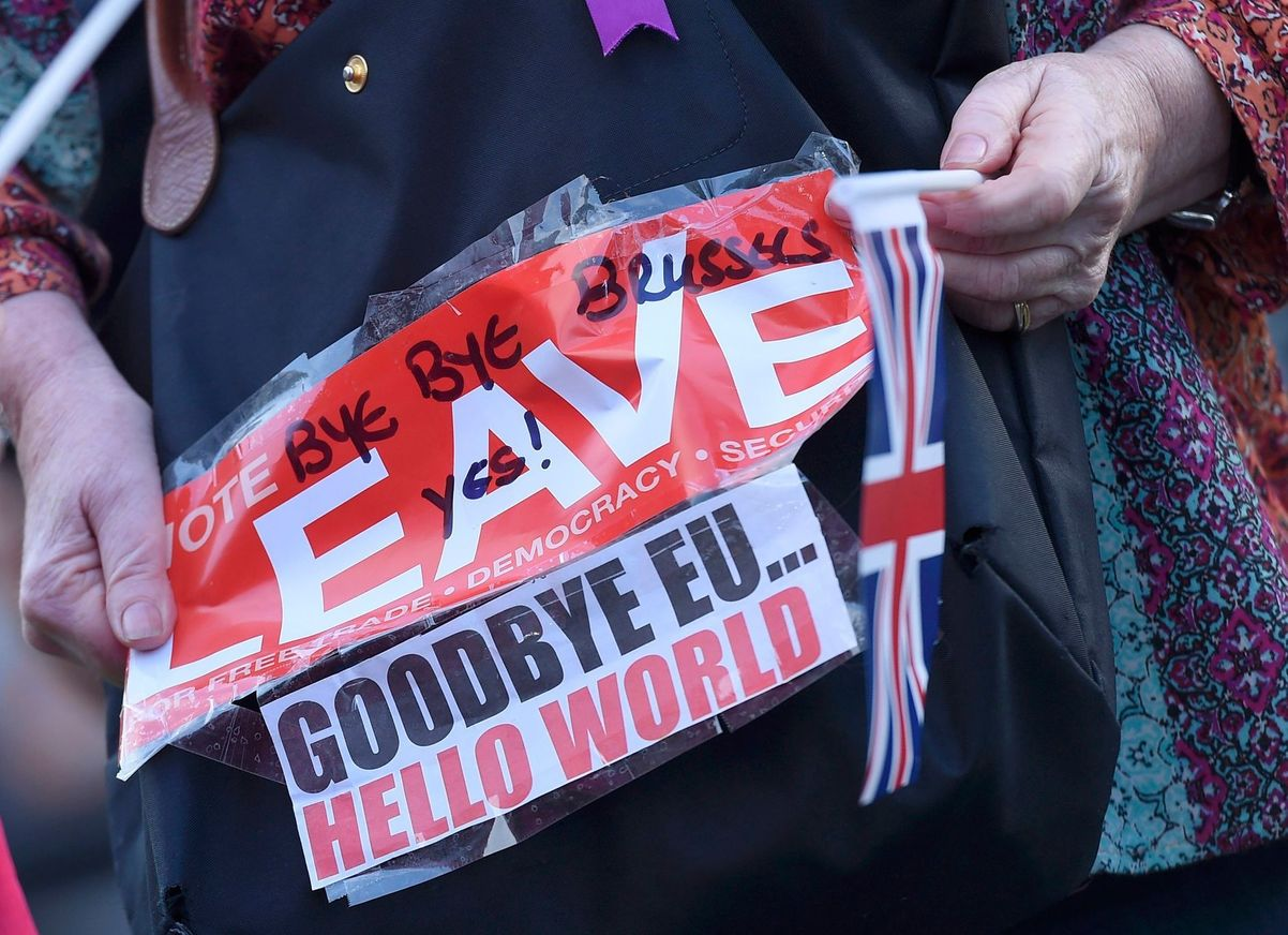 Brexit A vote leave supporter holds a poster in Westminster, London