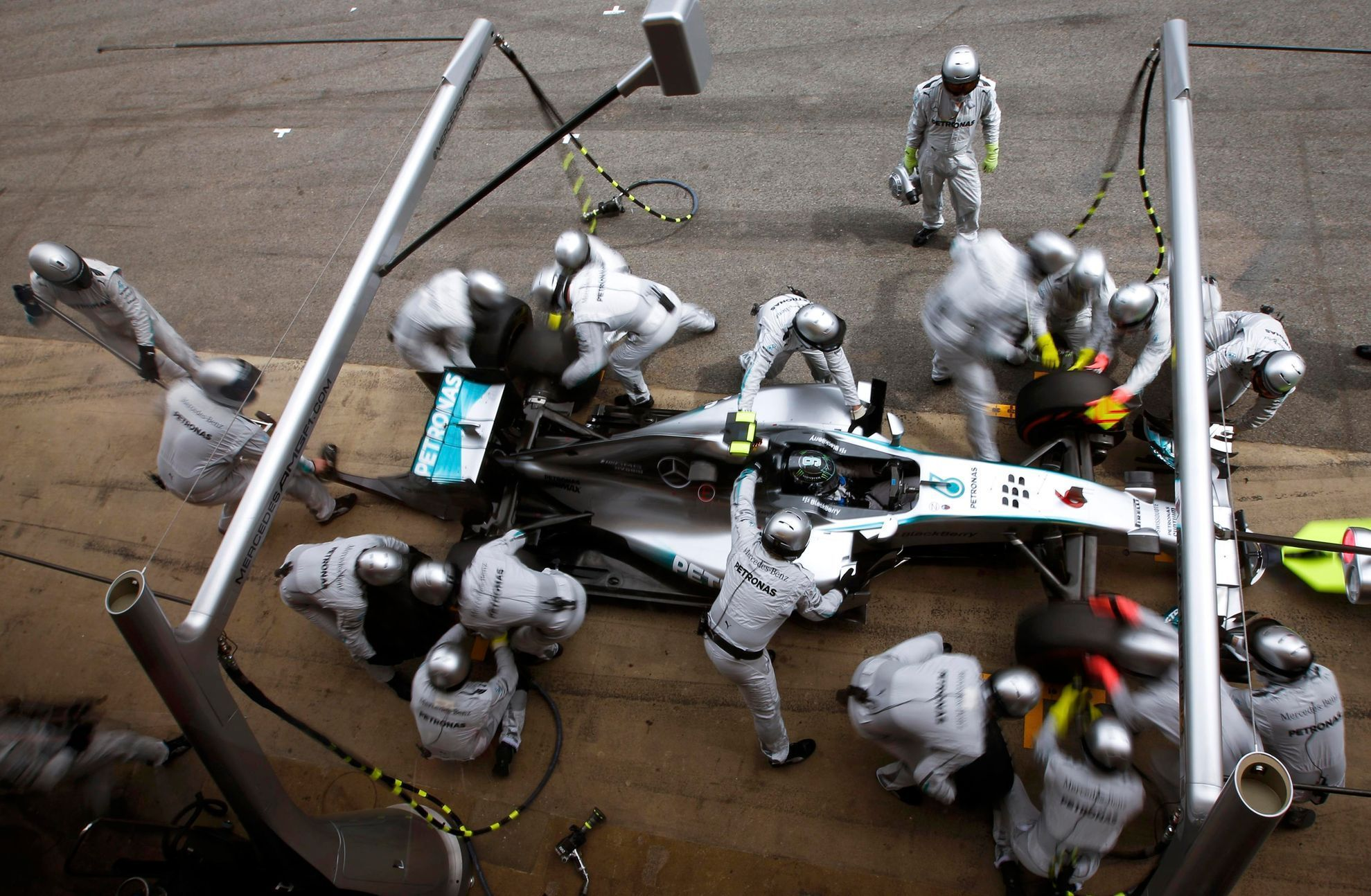 Crew members of Mercedes Formula One driver Rosberg of Germany service the car at pit stop during the Spanish F1 Grand Prix at the Barcelona-Catalunya Circuit in Montmelo