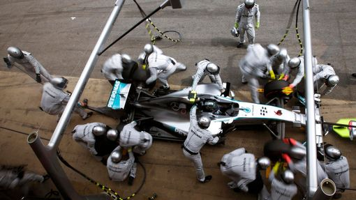 Crew members of Mercedes Formula One driver Nico Rosberg of Germany service the car at pit stop during the Spanish F1 Grand Prix at the Barcelona-Catalunya Circuit in Mon