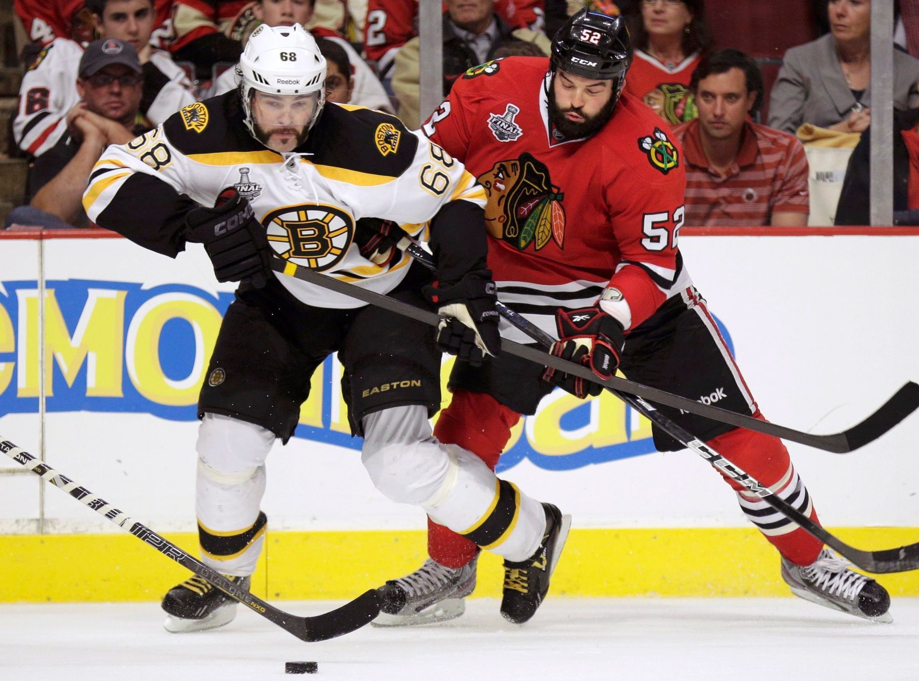 Bruins' Jagr is checked by Blackhawks' Bollig in double-over