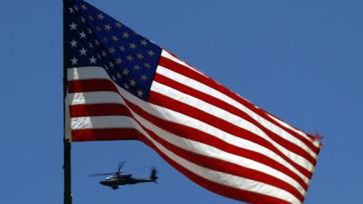 A U.S. Army Apache helicopter flies past a flag on Observation Post Mustang in Afghanistan's Kunar Province June 4, 2012. REUTERS/Tim Wimborne (AFGHANISTAN - Tags: CIVIL