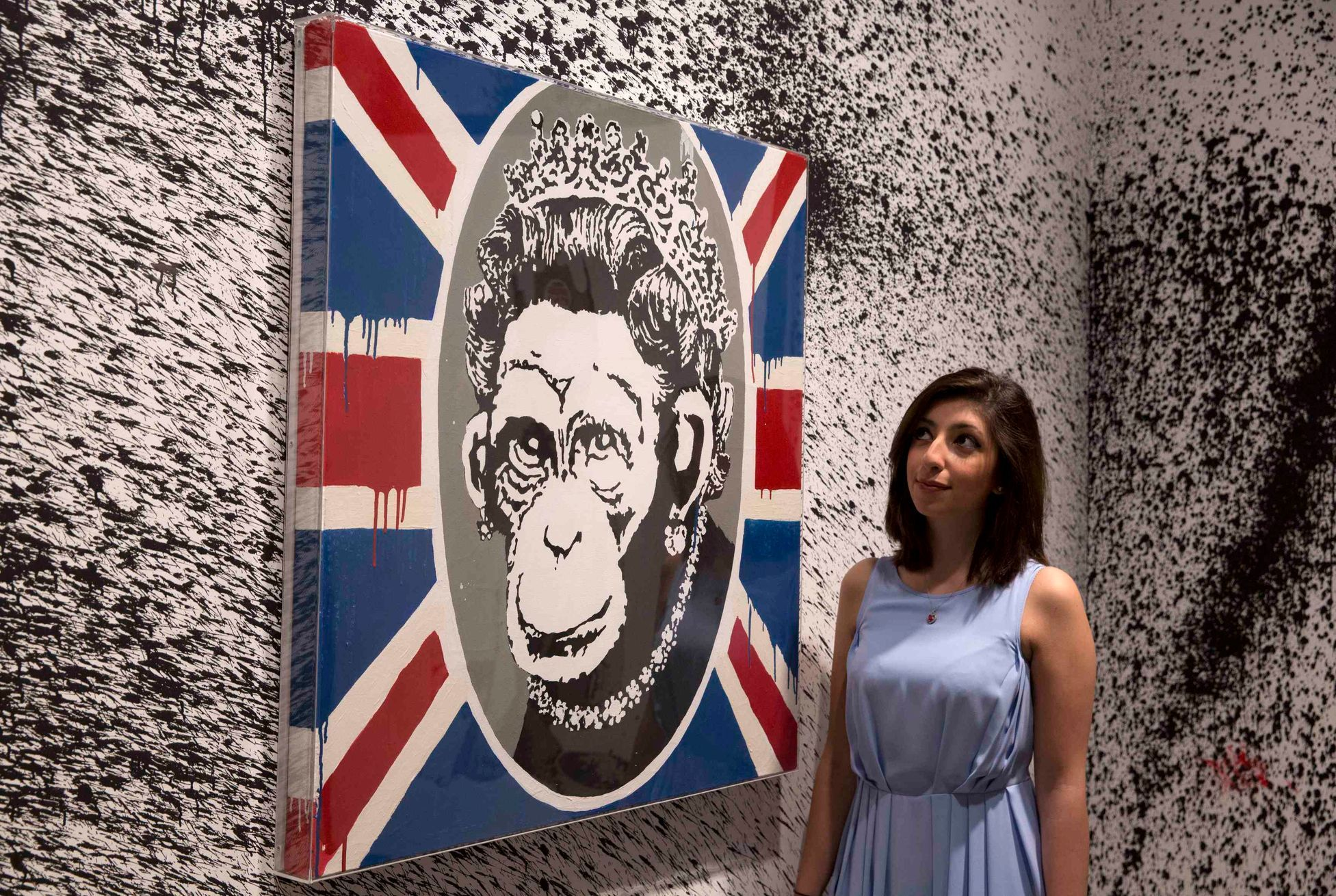 "A gallery assistant poses with work ""Monkey Queen"" at the Banksy: The Unauthorised Retrospective at Sotheby's S2 Gallery in London"