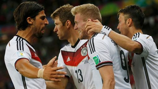 (L-R) Germany's Sami Khedira, Thomas Mueller and Mesut Ozil celebrate teammate Andre Schuerrle's (2nd R) goal against Algeria during extra time in their 2014 World Cup ro