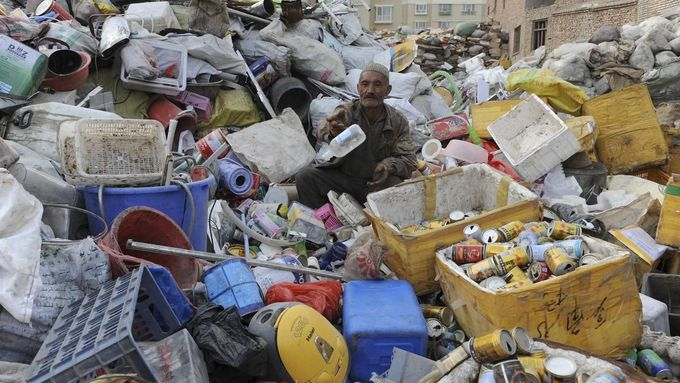 An elderly Uighur man sits on piles of garbage as he picks out the recyclable items at a recycling centre in Aksu